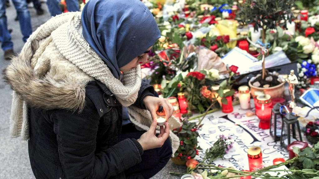 Млада мохамеданка запалва свещ пред френското посолство в Берлин. / Снимка: Минт прес нюз.