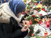 BERLIN, GERMANY - NOVEMBER 16:  A young Muslim woman lights a candle outside the French Embassy among candles, messages and flowers left by mourners commemorating the victims of last Friday's terrorist attacks in Paris that have left over 130 people dead on November 16, 2015 in Berlin, Germany. Eight Muslim organizations in Germany issued a common statement earlier in the day condemning the Paris attacks and citing Islam as a non-violent religion. The Islamic State (IS) claimed responsibility for the attacks and has vowed to launch more.  (Photo by Carsten Koall/Getty Images)