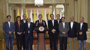 Президентът Хуан Мануел Сантос (в центъра) по време на обръщението си, заобиколен от своя екип в мирните преговори