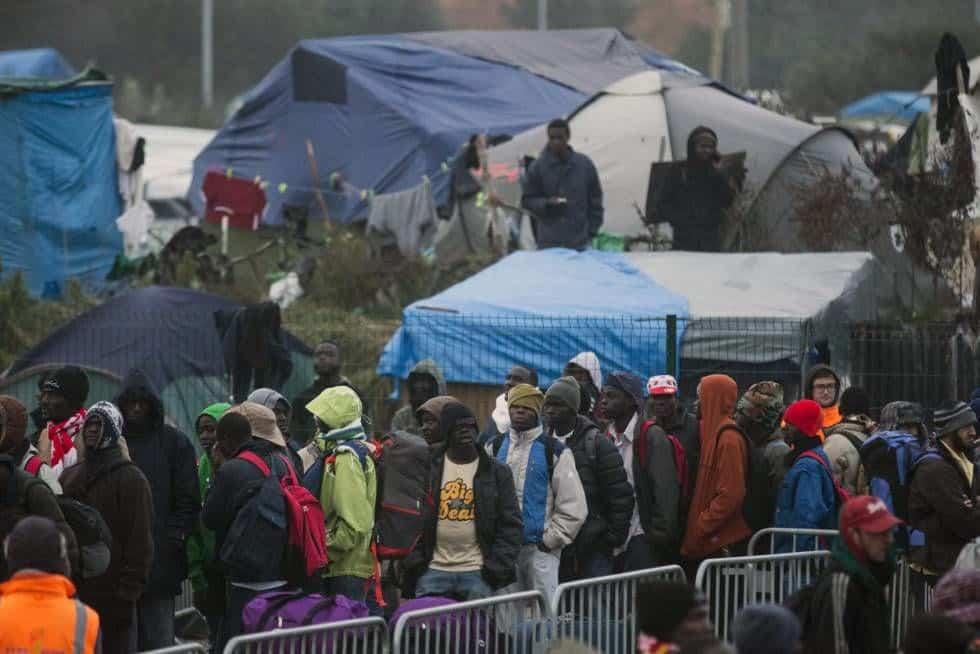 """Дългите опашки от мигранти, желаещи да напуснат """"Джунглата"""" край Кале, започват от самия лагер и стигат чак до разположения на около километър от него разпределителен хангар"""