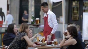 """Щастлив от заетостта си келнер обслужва летни туристки на площад """"Санта Ана"""" в Мадрид"""