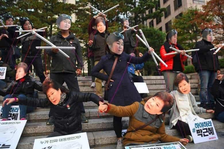 На протестите в Сеул президентката Пак Кън Хе е изобразявана като кукла на конци, управлявана от приятелката ѝ и шаманка Чхуe Сун Сил
