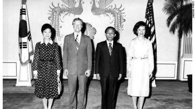 Като младо момиче Пак Кън Хе играе ролята на първа дама по време на управлението на баща си Пак Чжон Хи. Тук тя посреща заедно с него в Сеул през 1979 г. президента на САЩ Джими Картър и съпругата му