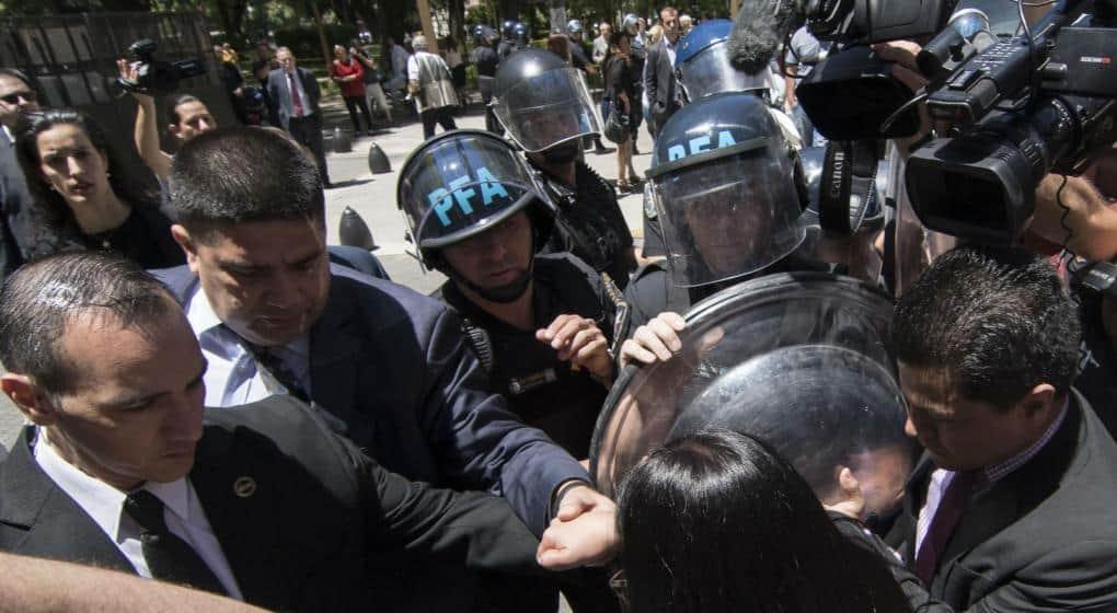 Женската глава в гръб на преден план е на Делси Родригес. Аржентински полицаи я дърпат за ръката.