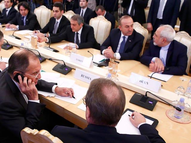 Край масата на тристранните преговори в Москва са Сергей Лавров (с телефона на преден план), както и колегите му от Турция и Иран–Мевлют Чавушоглу и Джават Зариф (срещу него)