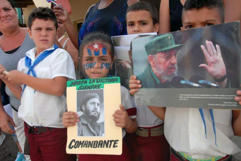 """Пионерчета отдават почит на траурния кортеж, а мвомиченцето най-отпред си е нарисувало на лцето кубинското знаме и надписа """"Аз съм Фидел""""."""