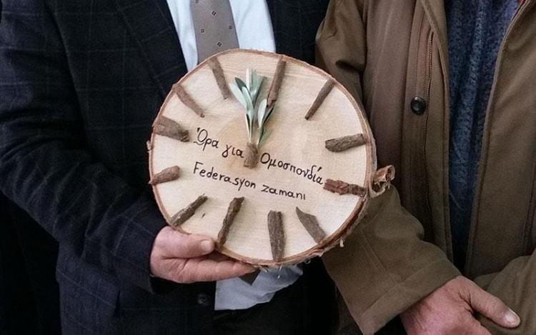 Часовник с маслинови клонки за отброяване на времето до обединението на Кипър връчиха представители на кипърските гръцки учителски съюзи на своите колеги кипърски турци при посещението си в техни училища, декември 2016 г.