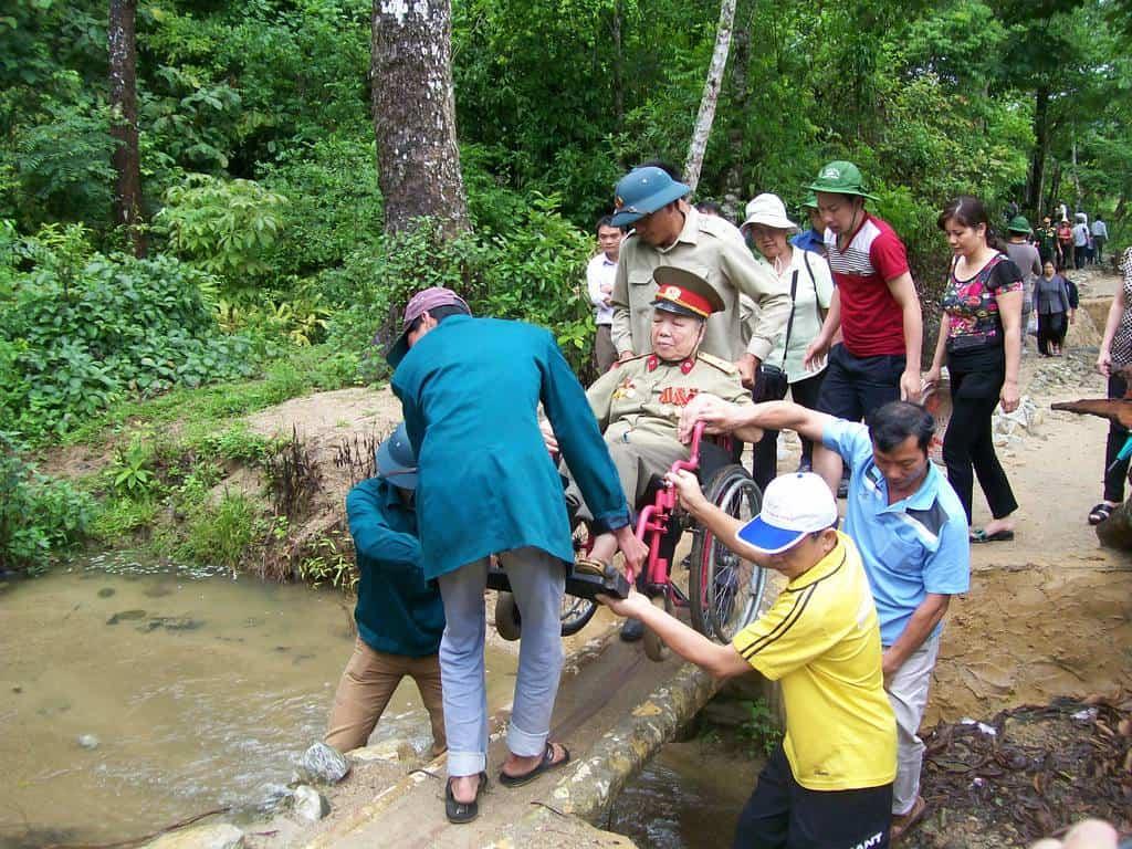 Посетители в мемориалния комплекс Фам Ле Нанг–горска дона, в която е бил разположен щабът на генерал Зиап, се хвърлят да пренасят през тясно мостче инвалидната количка на ветеранка от войните