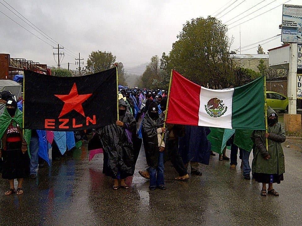 Шествие на сапатистки активисти издига наравно знамето на организацията и националния флаг на Мексико. Снимка: globalproject.info
