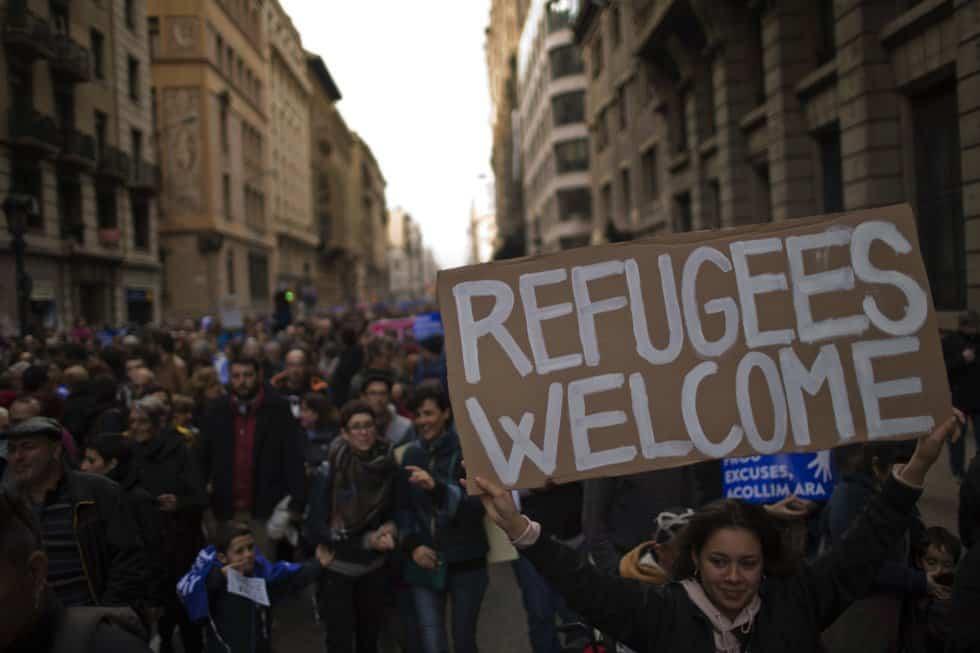 """Многохилядното шествие в Барселона дотолкова обърка някои нашенци, че предположиха да е било не ЗА, а ПРОТИВ мигрантите. Снимките обаче са достатъчно красноречиви. """"Бежанци, добре дошли!""""–пише на един от плакатите, издигнат на демонстрацията. Снимка: elpais"""