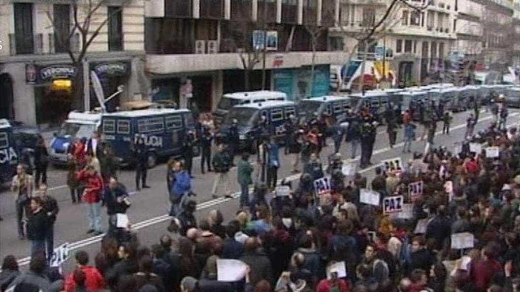 """Демонстранти размахват плакати с надписи """"Мир"""" на протест пред обградената от полиция централа на Народната партия в Мадрид след атентата от 11 март 2004 г. Снимка: rtve.es"""