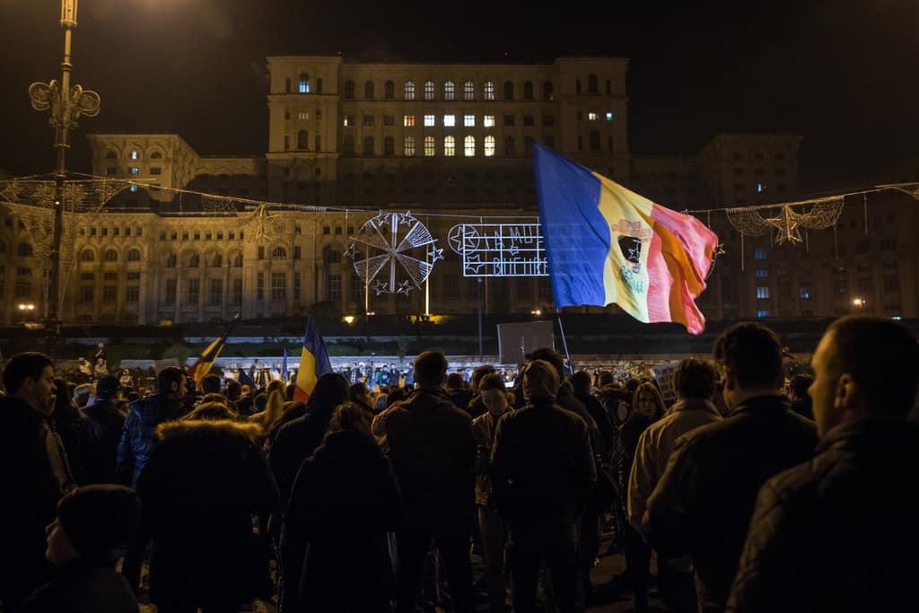 В центъра на Букурещ отново се развяват флагове с изрязани гербове, както и през 1989-та. Снимка: Ал-Джазира