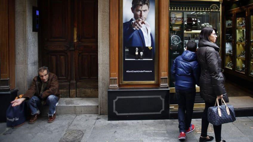 Социалната ножица между просяка и луксозния бижутериен магазин срязва и шансовете за здрав живот на милиони хора по света. Снимка: elpais.com