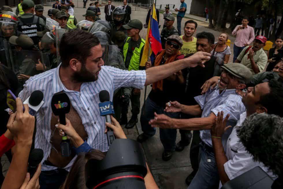 Депутат опозиционер със скъсана риза се заканва на опониращи му граждани чависти пред сградата на Върховния съд в Каракас и пред камерите и микрофоните на журналистите. Снимка: ЕФЕ