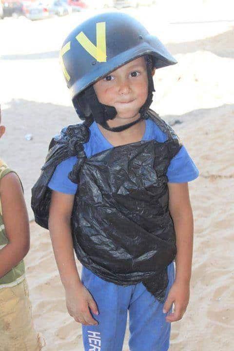 """Несма е публикувала в своя Туитър тази снимка от Газа, направена през 2014-та, като пояснява, че при онези бомбардировки Израел е убил 18 журналисти, """"след като ги демонизира"""". А децата си играели със защитните каски на репортерите. Както личи от снимката, очевидно са си правели и """"бронежилетки"""" от найлонови торбички. Снимка: Туитър"""