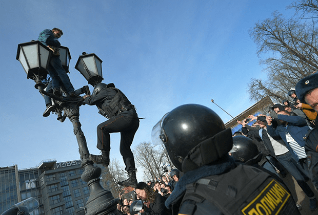 """Полицай се катери по улична лампа, за да свали качилите се на нея младежи на площад """"Пушкин"""" в Москва. Снимка: Коммерсантъ"""