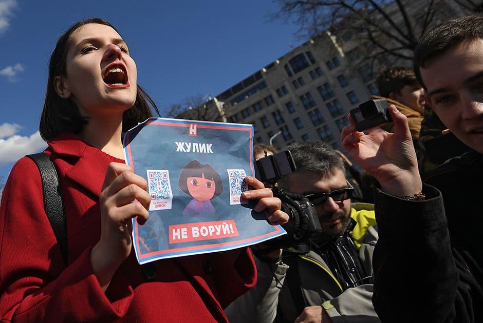 Млада учасничка в протестите носи плакат срещу корупцията. Снимка: РИА