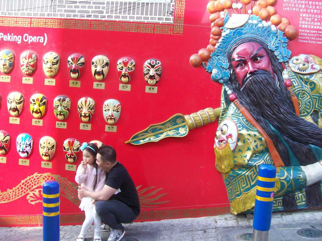 Татко и дъщеричка на фона на колоритна реклама за традиционна Пекинска опера с маски. Снимка: Къдринка Къдренова