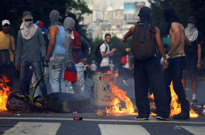 """Маскирани """"демонстранти"""" край направено от тях заграждение на кръстовище в Каракас. Снимка: albaciudad.org"""