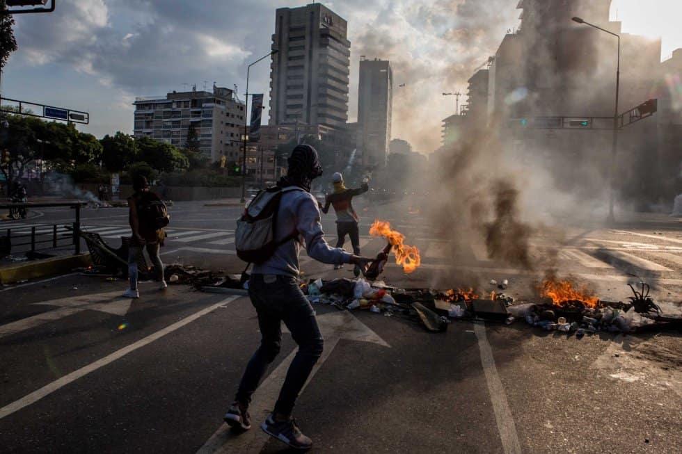 """Демонстранти мятат коктейли """"Молотов"""" по полицаи в източната част на Каракас. Снимка: ЕФЕ"""