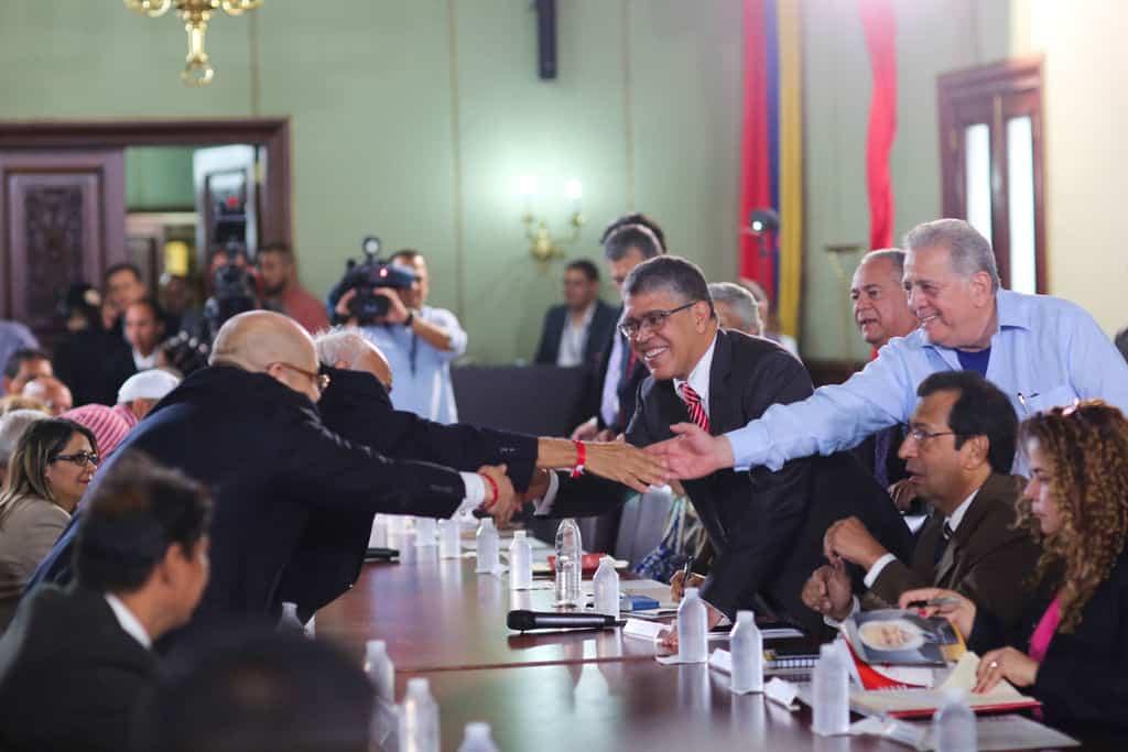 Елиас Хауа (вдясно, наведен през масата за ръкуване, с очила и в костюм) по време на срещата с представители на 17 опозиционни партии с цел установяване на национален диалог. Снимка: resumenlatinoamericano