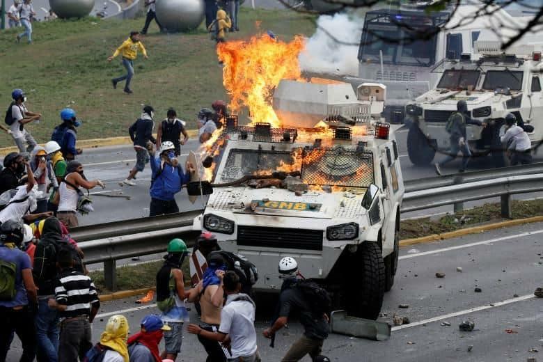 Опозиционни демонстранти атакуват и палят полицейска камионетка. Снимка: Туитър