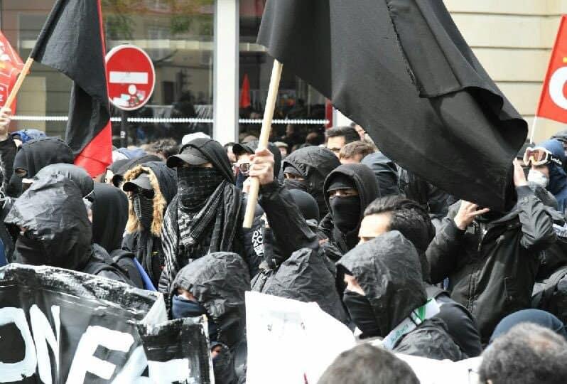 В първомайските прояви в париж се включиха и маскирани участници в черно, част от които предизвикаха сблъсъци с полицията. Снимка: Prefecture de Police de Paris
