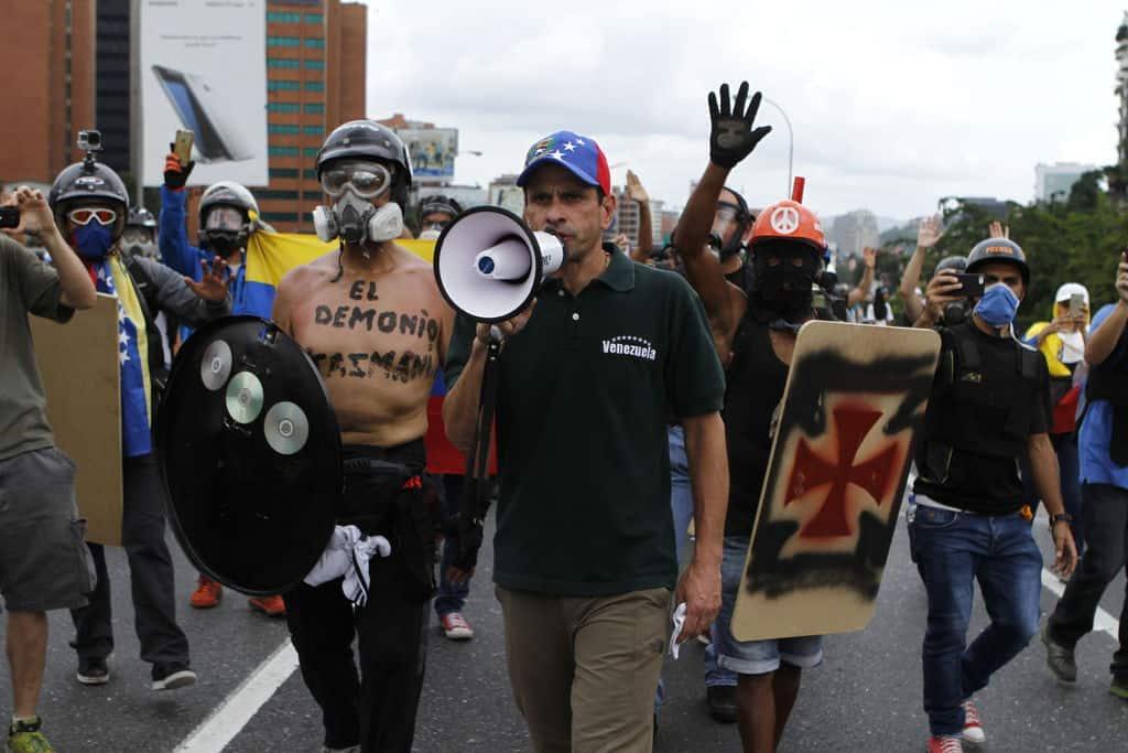 """В средата с високоговорителя е опозиционният водач Енрике Каприлес. Отляво негов съратник-протестър се е обозначил върху голия си торс като """"Тасманийският дявол"""". А вдясно почитател явно на тевтонците и на нацистките ордени си е нарисувал символа им върху самоделния щит. Снимка: albaciudad"""