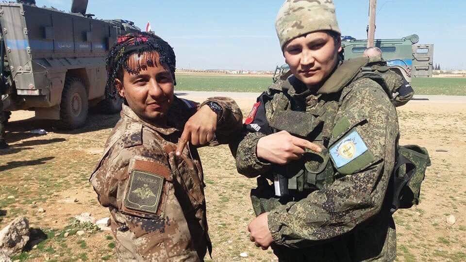 Кюрдски и руски бойци разменят баджовете си. През март руски и сирийски войски бяха демонстративно пратени в контролираните от кюрдите територии на Запад от град Манбидж, за да предотвратят атака от страна на Турция. Снимка: https://twitter.com/a_ozkok