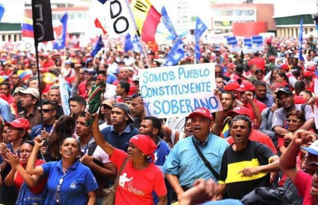 """Симпатизанти на правителството на Николас Мадуро участват в шествие в подкрепа на изборите за Конституционно събрание във венесуелската столица Каракас. На плаката отпред пише: """"Ние сме конституционен и суверенен народ"""". Снимка: Radio Nuevo Mundo"""