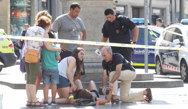 "Хора се опитват да помогнат на жена, пострадала при нападението на ""Рамблас"". Снимка: El Pais"