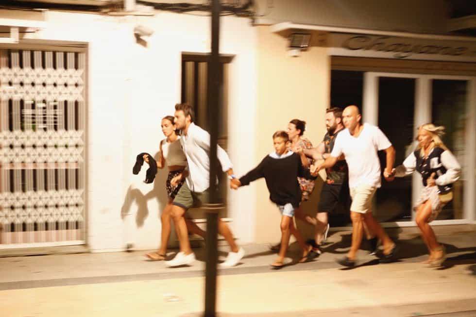 Ужасени туристи бягат по улица в Камбрилс, изпълнявайки искането на полицията да се укрият. Снимка: El Pais