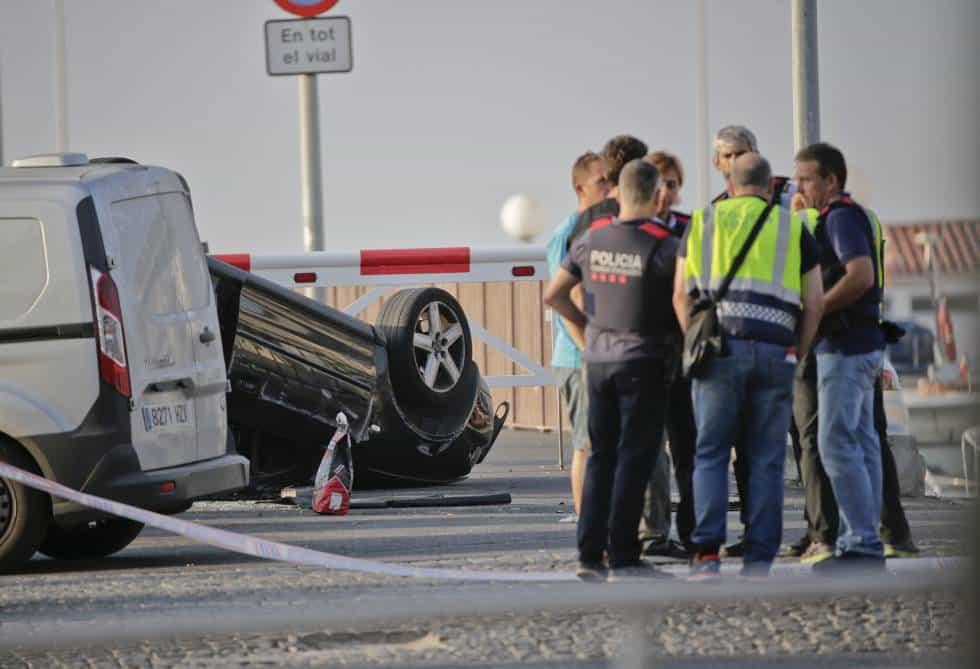 Полицаи край преобърнатата кола на атентаторите на следващия ден след нападението в Камбрилс. Снимка: EFE