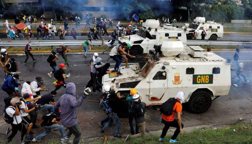 """""""Мирни"""" демонстранти по улиците на Каракас атакуват блиндирани коли на жандармерията. Препечатка от El Pais"""