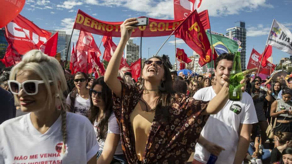 Правенето на селфита с бира в ръка по време на наподобяващите карнавалите протестни шествия засега не върши много работа. Снимка: El Universal