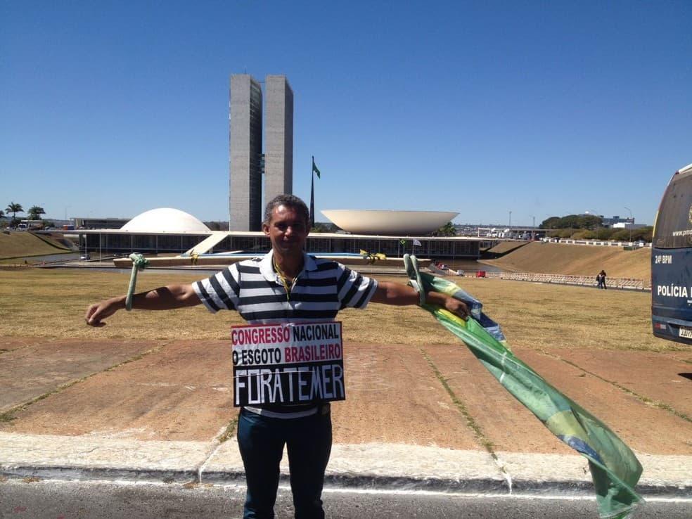 Този бразилец, който от месеци обикаля из страната, разпънат като Христос, протестираше самотно през деня, в който в Конгреса (на заден план) вървяха дебатите за съдбата на президента Мишел Темер. Снимка: grupobomdia.com.br