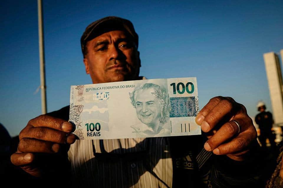 Още един протестиращ усърдно показваше на фоторепортерите фалшива банкнота с образа на Мишел Темер. Снимка: Resumen Latinoamericano