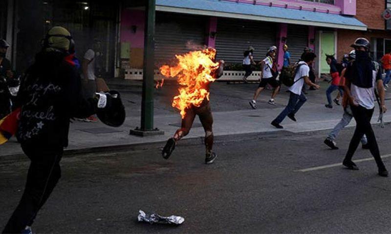 Горящият като жива факла Орландо Фигера бяга от уличните си екзекутори. Снимка: Туитър