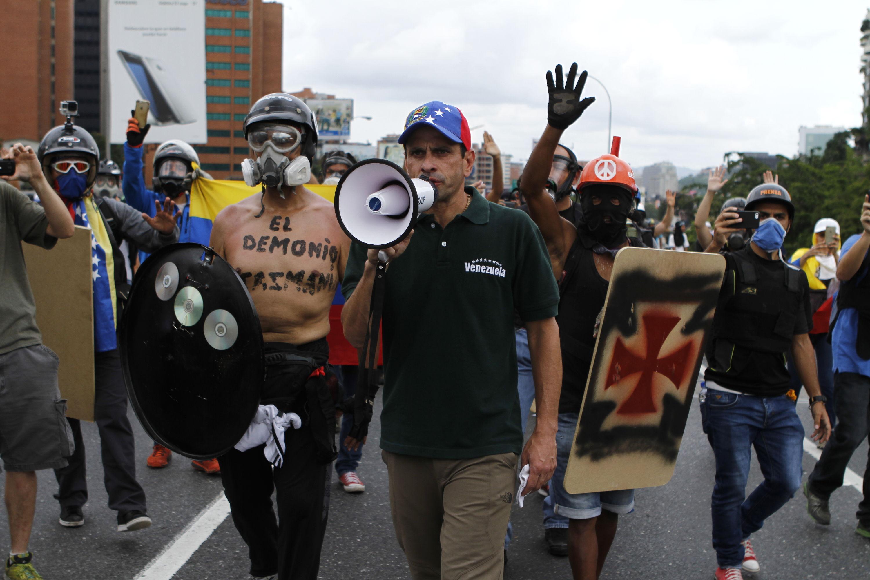 Венесуелският опозиционен водач Енрике Капролес (с мегафона) нахъсва протестиращи по време на антиправителствените безредици в Каракас през май т.г. Снимка: Resumen Latinoamericano