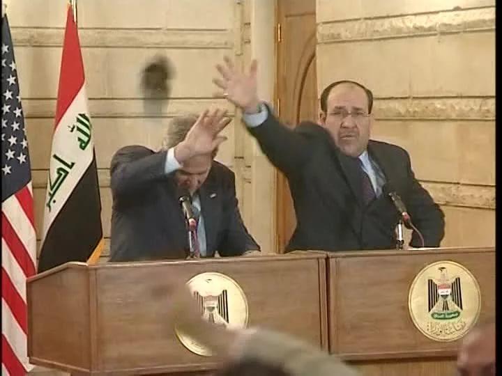 Втората обувка също полита към Буш, Ал-Малихи гледа да предпази госта си с ръка, но и самият Буш умело се пази. Снимка: Youtube