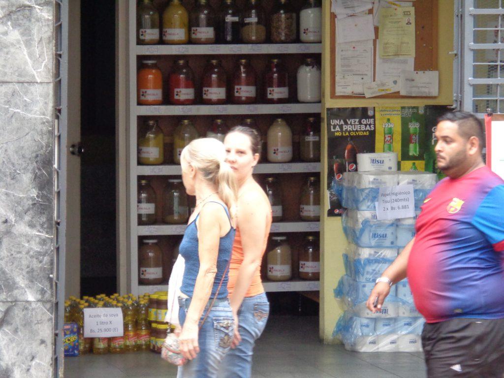 Зад минувачите се вижда асортиментът на това квартално магазинче в Каракас. Вдясно, зад едрия мъж, има купчина с тоалетна хартия по 6 881 боливара за две ролки. А долу вляво са стековете със соево олио–по 25 900 боливара за литър. Снимка: Къдринка Къдринова