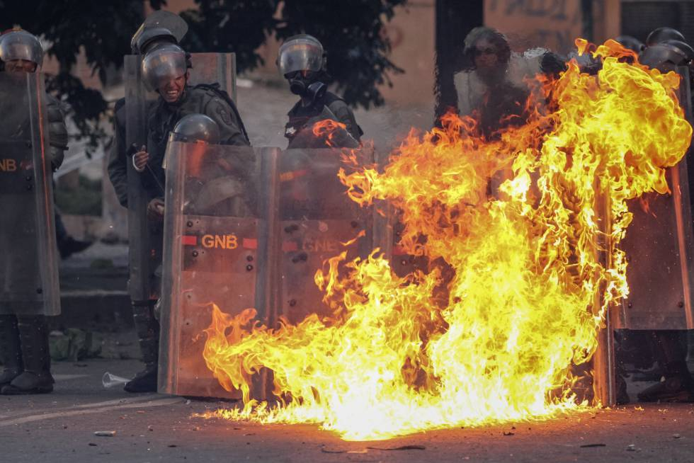"""Метнат срещу служители на Боливарската национална гвардия коктейл """"Молотов"""" избухва в пламъци пред редицата им по време на миналогодишните безредици."""