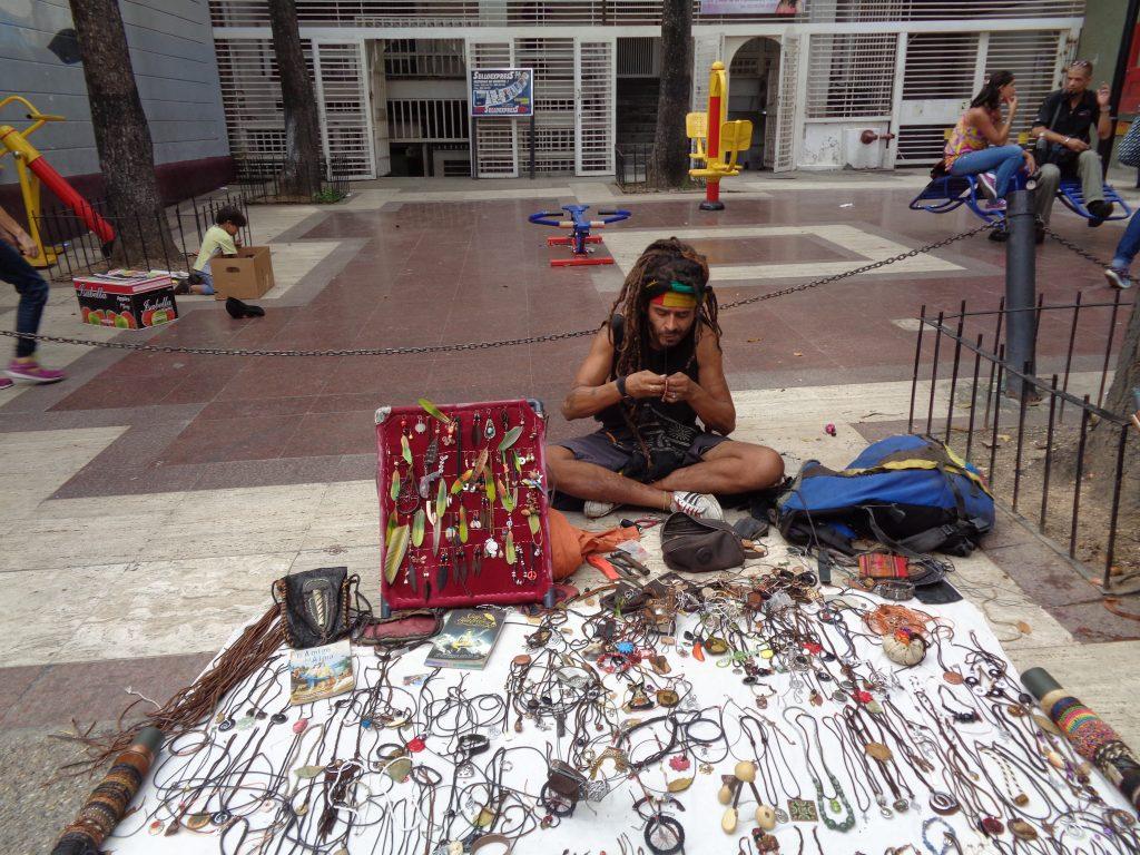 """Този младеж продължава да плете гривнички, докато продава изработени от самия него украшения от еко-материали на улица в """"Либертадор"""". Снимка: Къдринка Къдринова"""