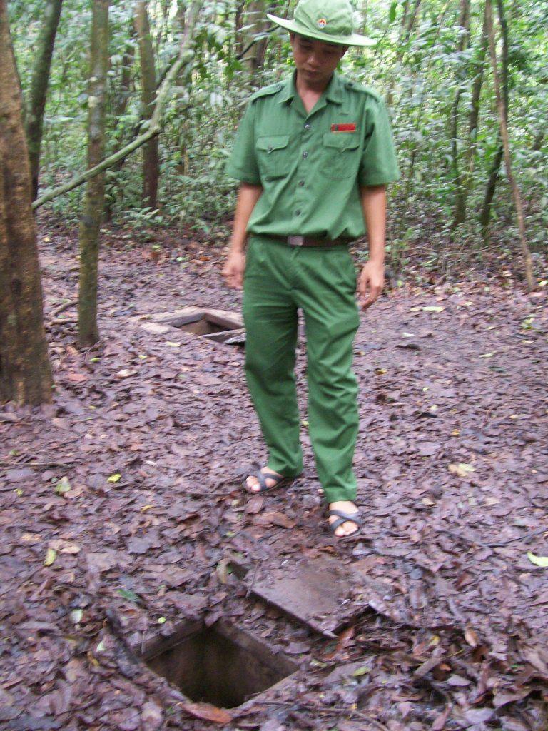 Екскурзовод, облечен като боец на виетнамската Народна армия, показва на туристи в гората край Ку Чи вход към един от партизанските тунели. Снимка: Къдринка Къдринова