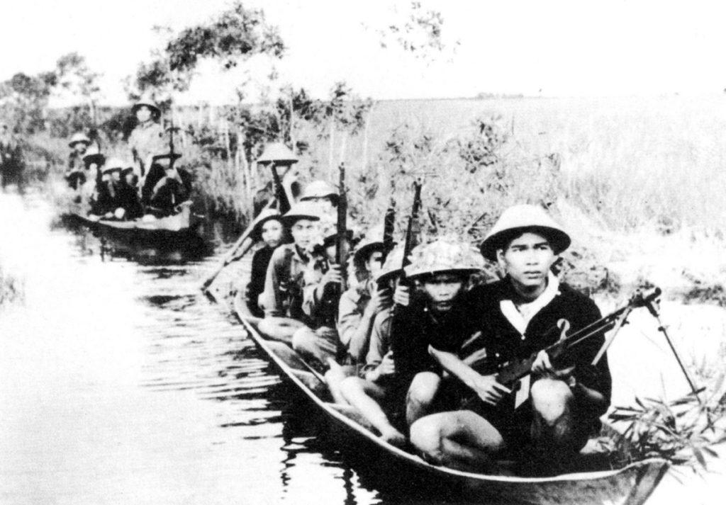 Южновиетнамски партизани се придвижват с лодки, за да атакуват противника. Снимка: VNA