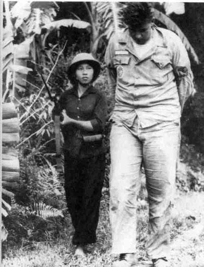 Този кадър също става исторически–дребна виетнамска партизанка води едър американски пленник. Снимка: VIA