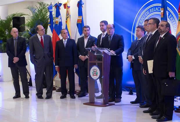 """Водачът на опозиционната делегация в Доминиканската република Хулио Борхес (зад катедрата) обяви в последния момент, че няма да подпише споразумението, защото то """"не е достойно за венесуелския народ"""". Снимка: caracaschronicles"""