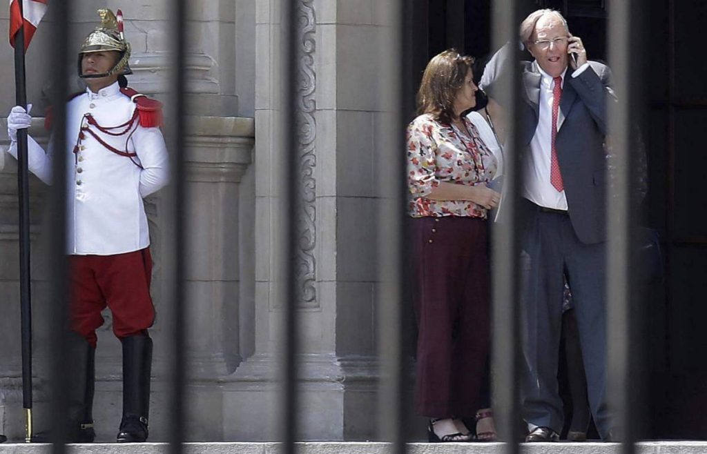 Педро Пабло Кучински (вдясно) си тръгва след оставката си от президентския дворец в Лима, говорейки по мобилния телефон. Изпращат го само няколко служителки. Снимка: El Pais