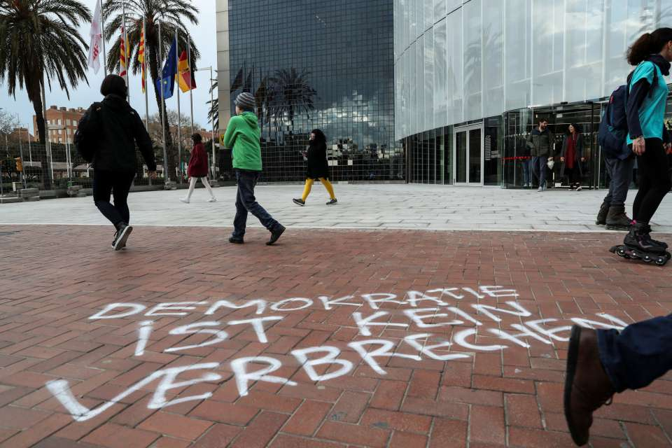 """""""Демокрацията не е престъпление"""" е написано на немски върху тротоара пред германското консулство в Барселона. Снимка: EFE"""