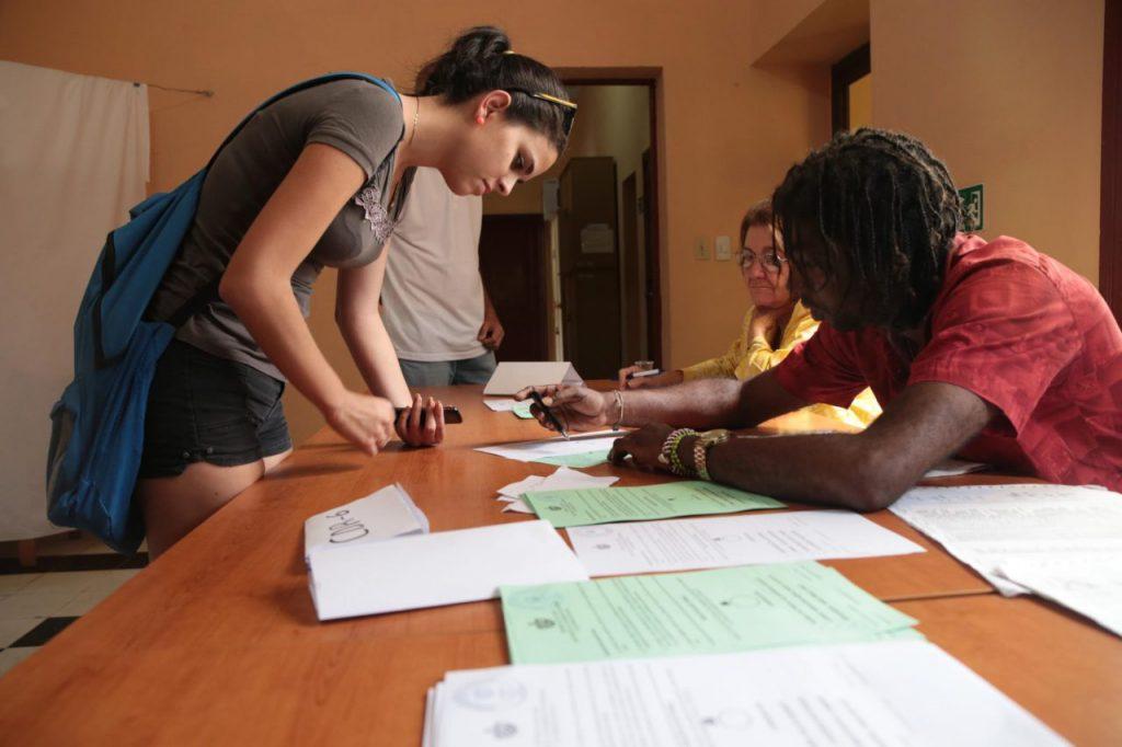 Млада кубинска гласоподавателка се отбелязва в изборните списъци преди да даде вота си. Снимка: Resumen Latinoamericano